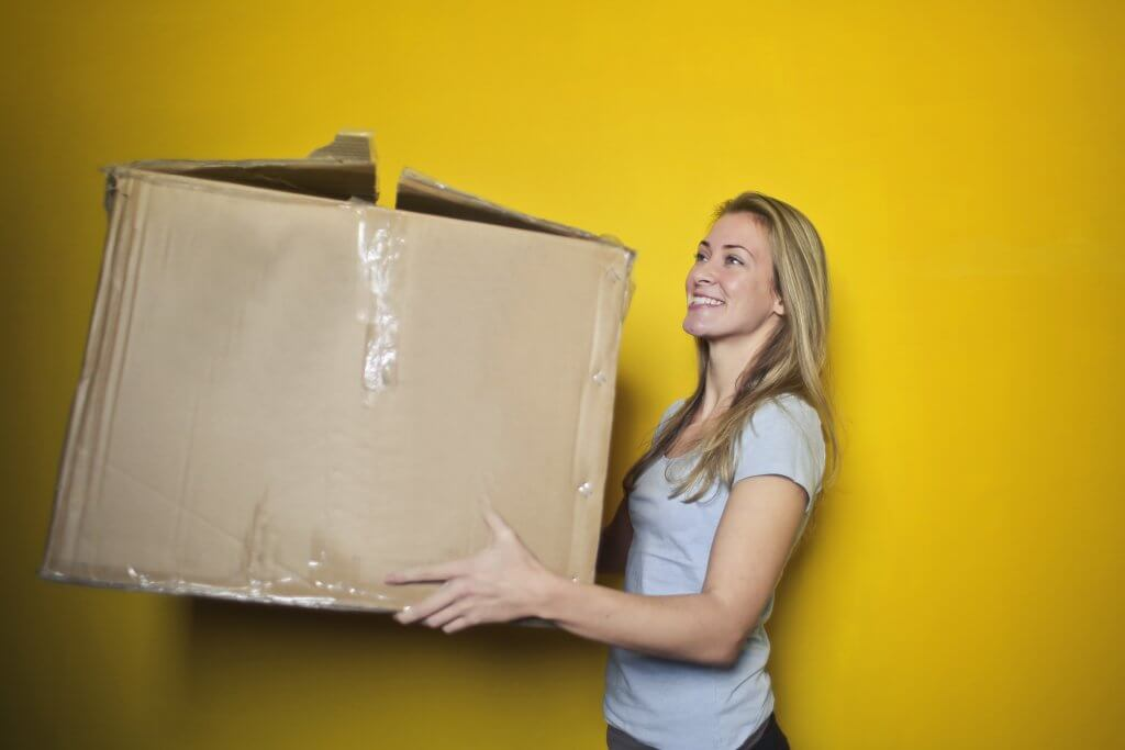 smiling woman holding decrepit cardboard box