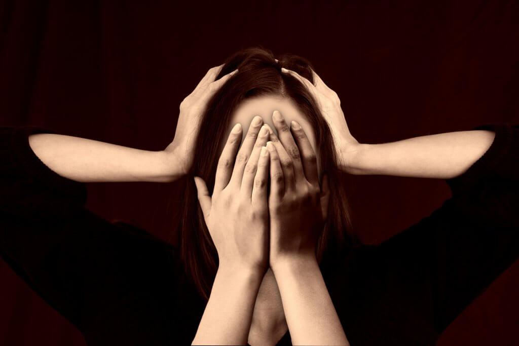 woman covering her face with another pair of hands holding her head