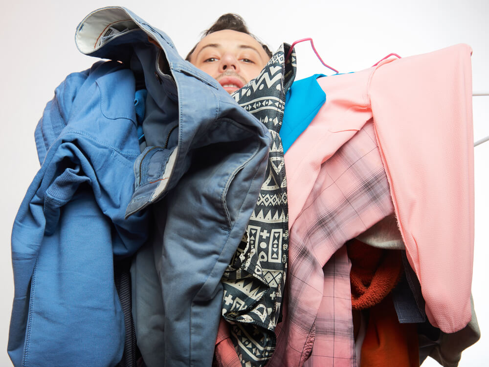 Man under a pile of clothes