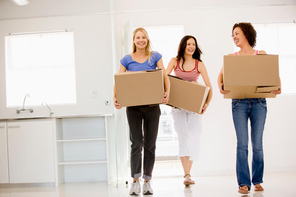 three women carrying cardboard boxes