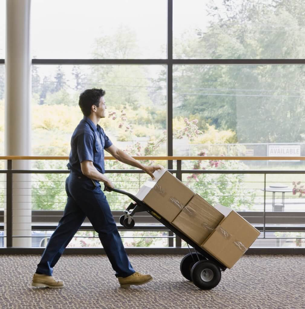 man moving boxes on hand truck