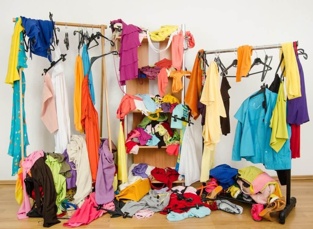 closet shelving and rods covered haphazardly with clothes