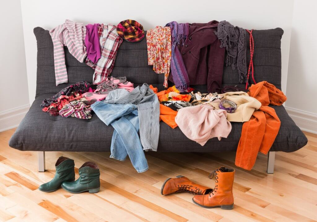 couch covered in clutter and clothes