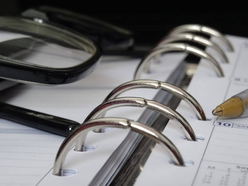 closeup of glasses and pen resting on planner