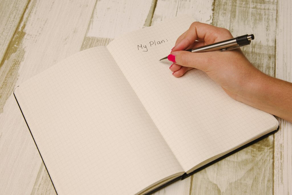 woman's hand writing in planner