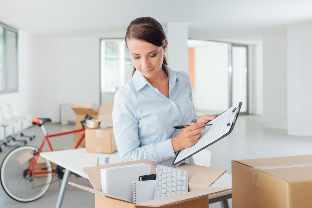 woman looking into box while holding clipboard