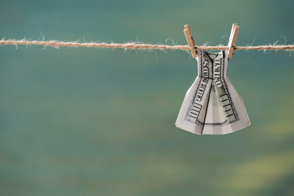 money folded in the shape of a dress hanging on a clothesline