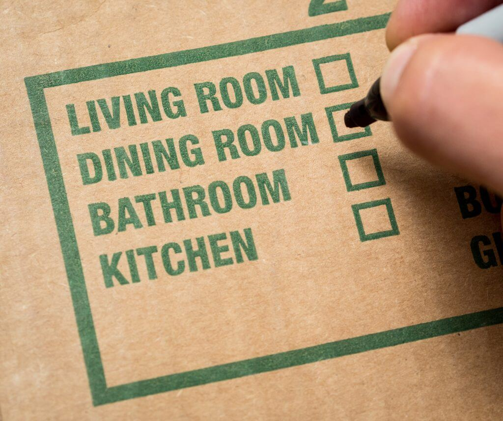 "hand with marker about to check ""dining room"" box on cardboard box"