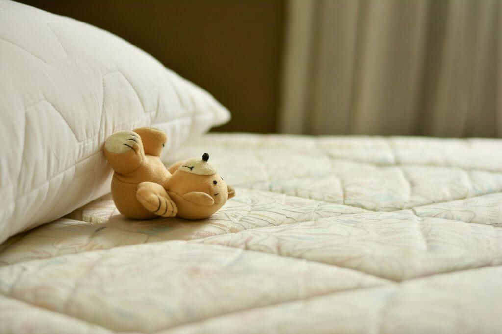 teddy bear on mattress with no sheets