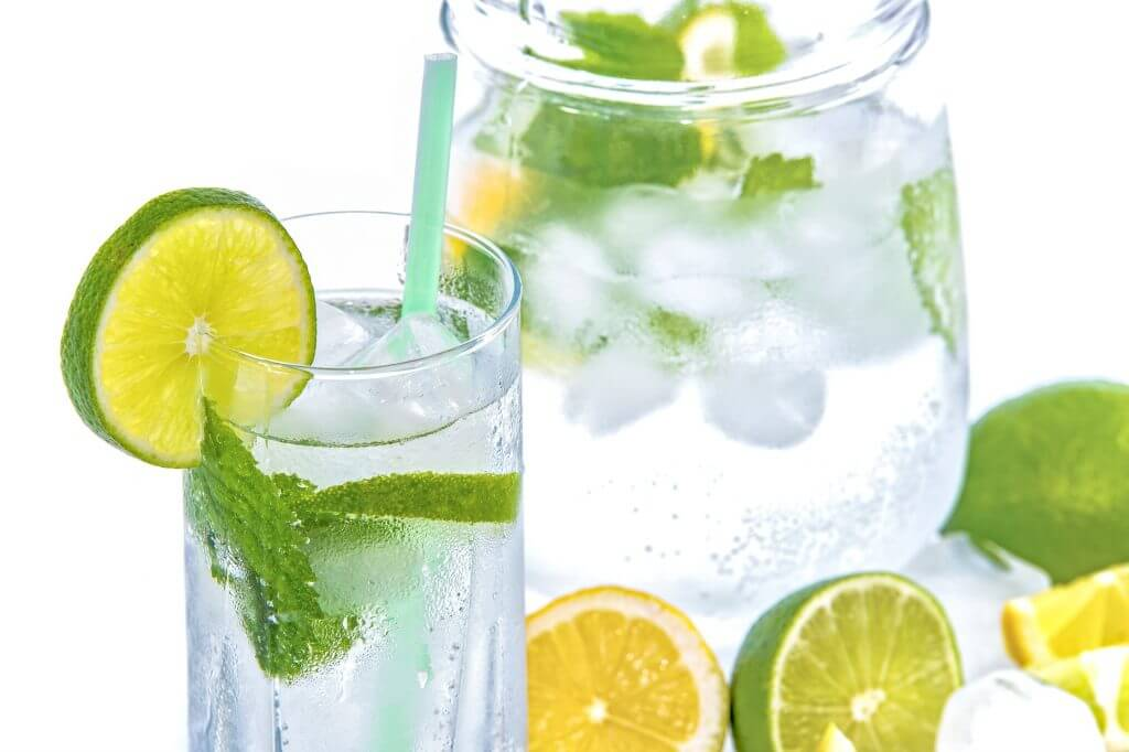 pitcher and glass of water with mint and lime