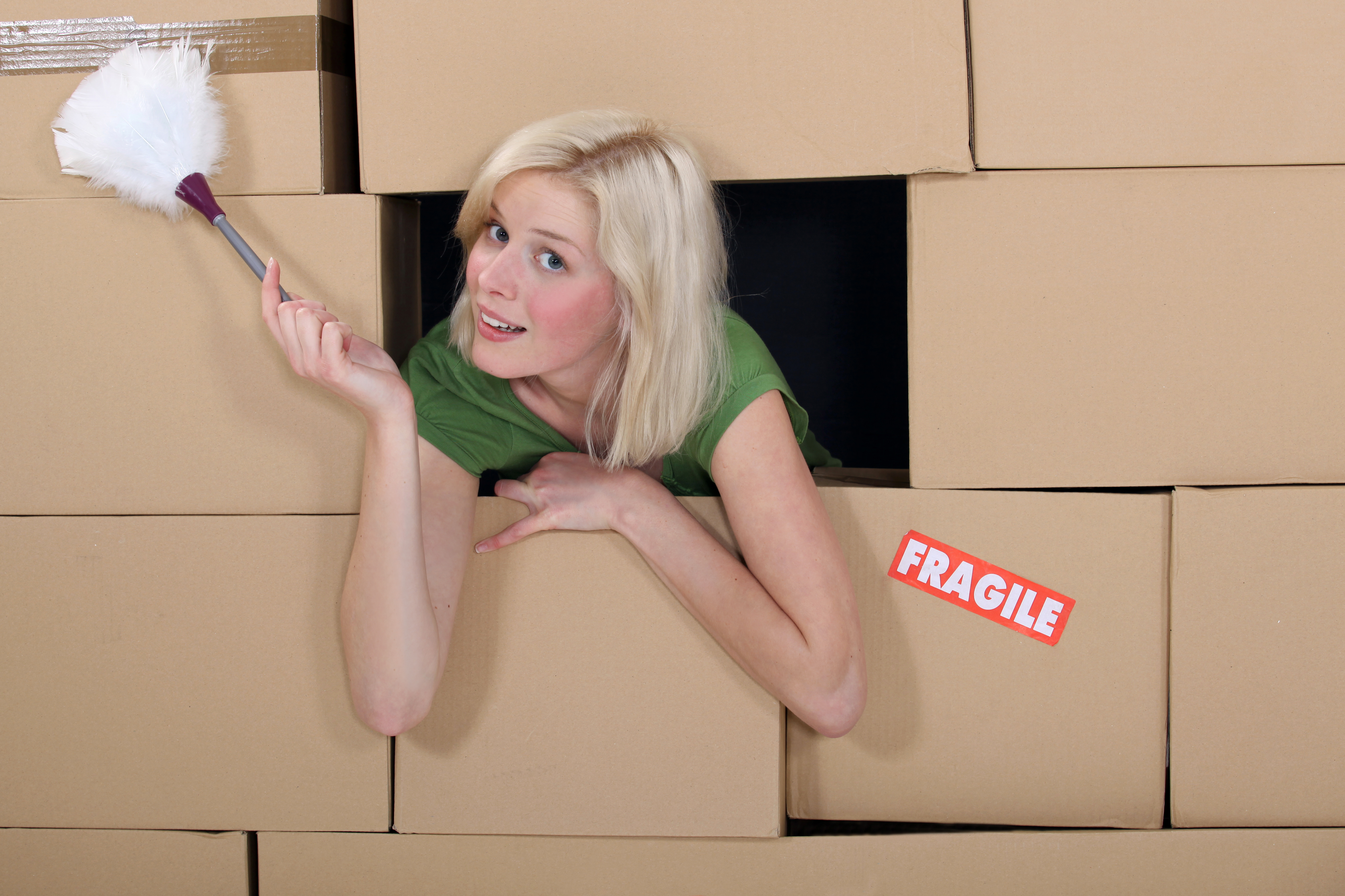 overwhelmed woman with duster surrounded by boxes