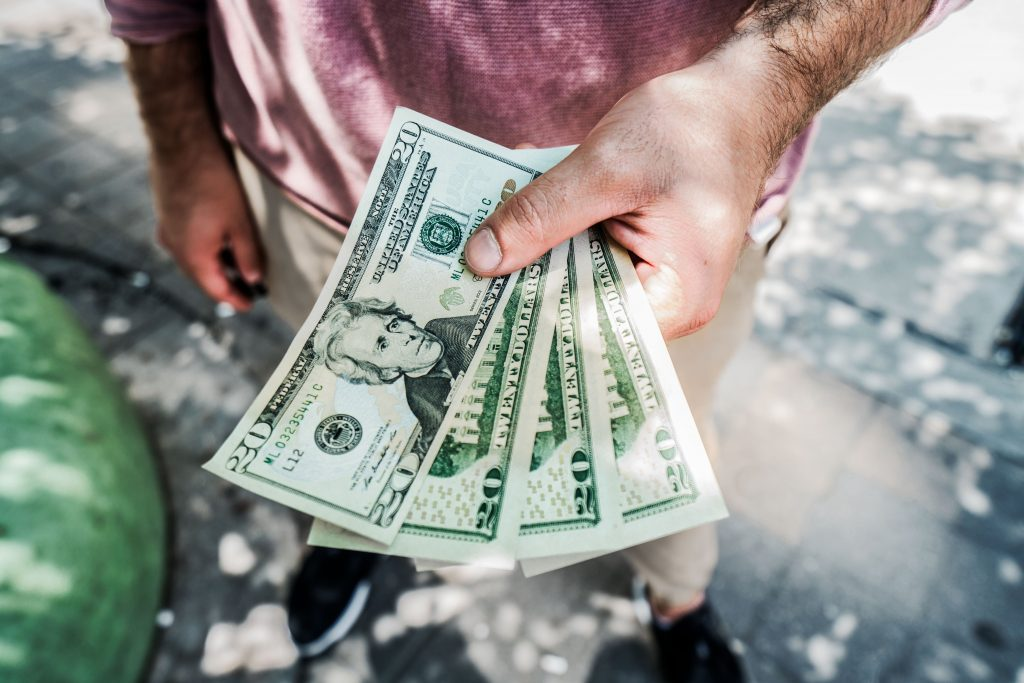 man's hand holding out four 20 dollar bills