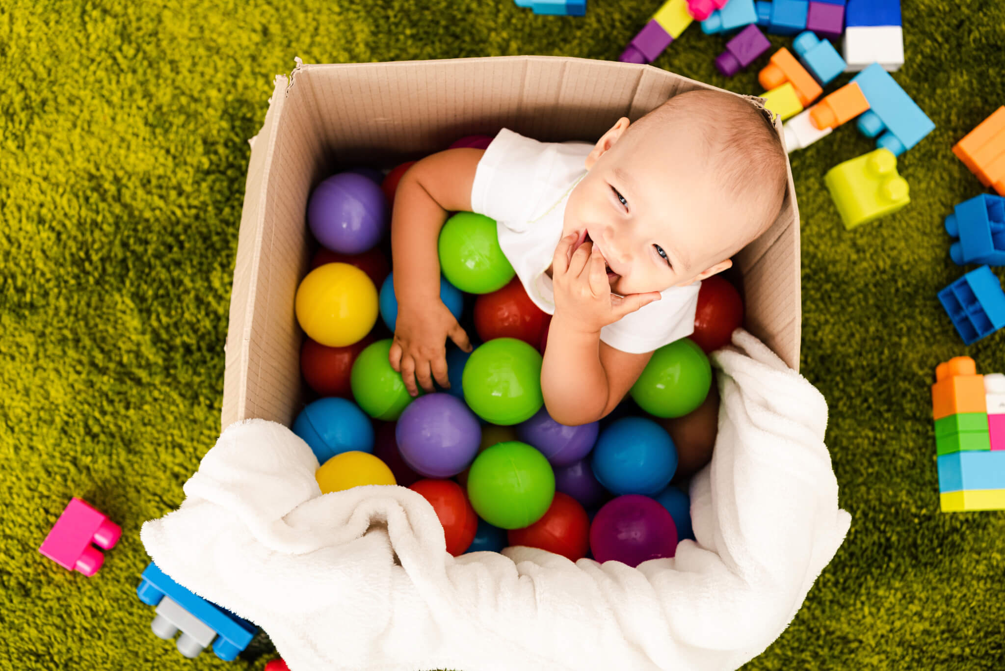 baby in box filled with colorful balls
