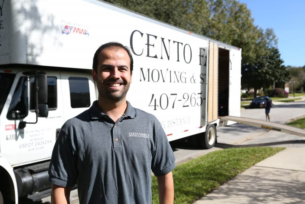 smiling mover next to Cento Family Moving truck