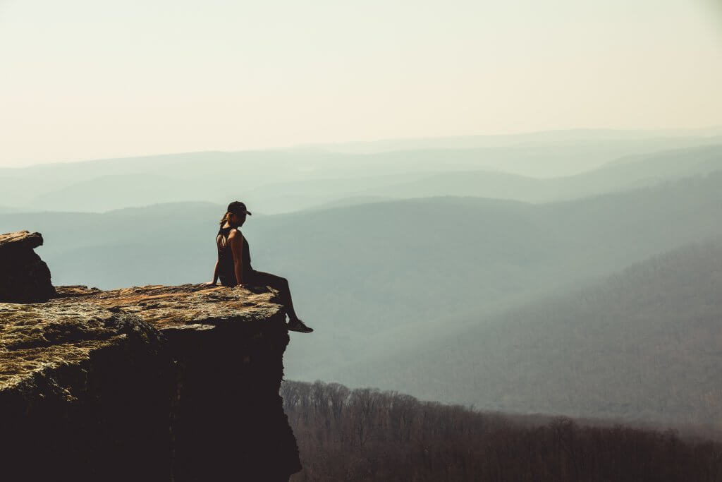 woman on edge of cliff overlooking the Ozarks