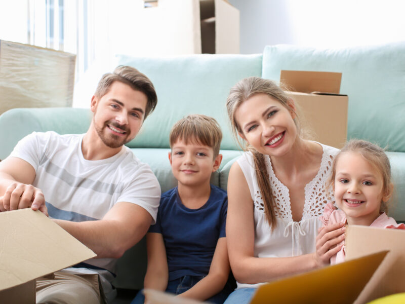 Young couple with children resting near boxes indoors. Happy family on moving day