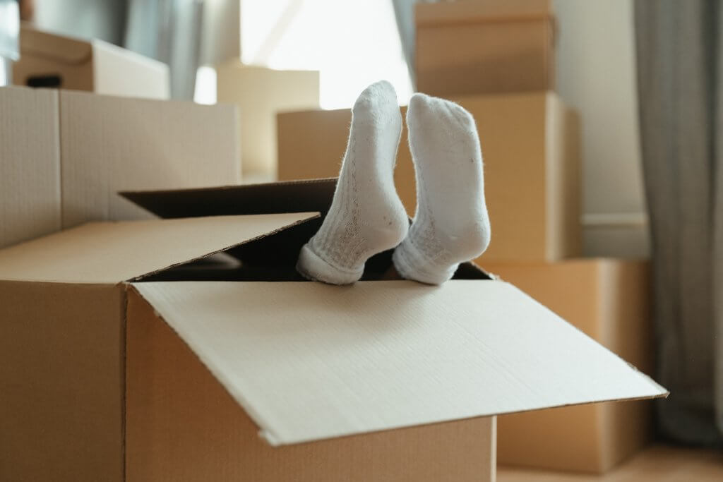 child's feet sticking out of cardboard box